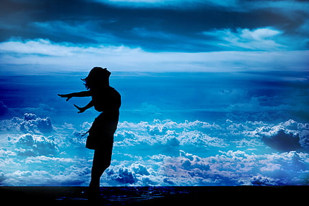 silhouette of standing woman while spreading her arms sideward