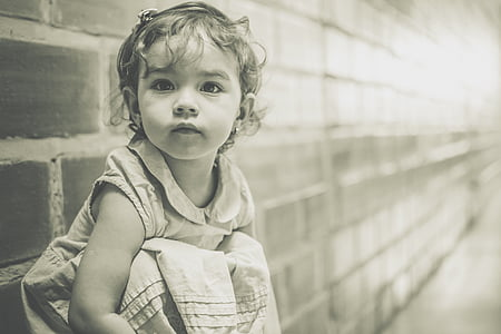 grayscale photo of girl sitting against brick wall
