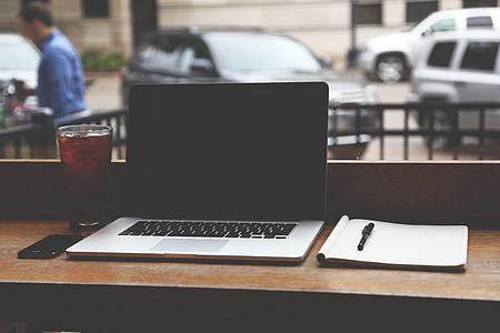 MacBook pro beside notebook and pen