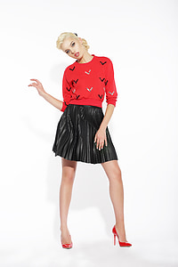 woman wearing red and black sweatshirt and pleated black skirt