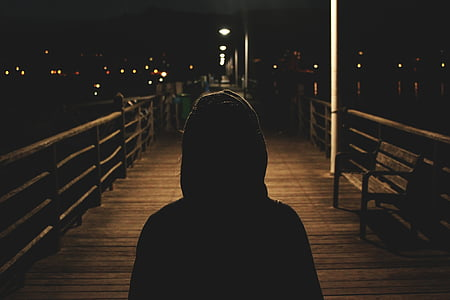 photo of person's silhouette standing on wooden ground