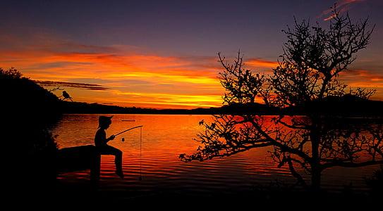 silhouette of boy fishing on dock