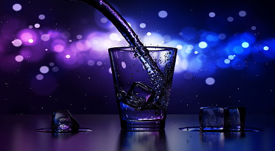 liquid being pour on clear glass shot glass