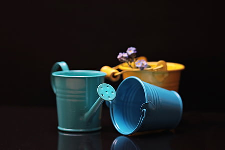 green watering can beside blue and yellow buckets
