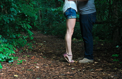 couple standing in the middle of forest during daytime