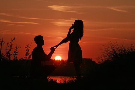 silhouette of man holding ring to woman