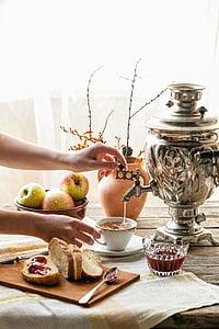person holding gray samovar tea urn