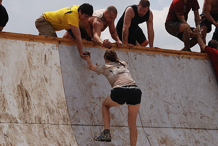 woman climbing on wall and two man helping