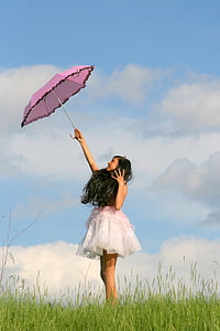 woman in pink and white sleeveless dress holding pink umbrella