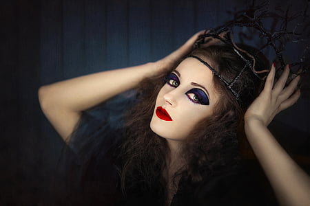 brown haired wearing black crown with black background