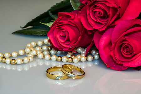 white and gold pearl necklace beside two gold-colored wedding bands and pink roses