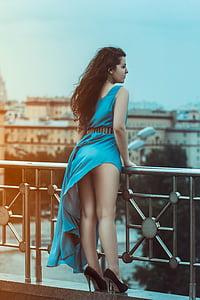 woman wearing blue sleeveless high-low dress