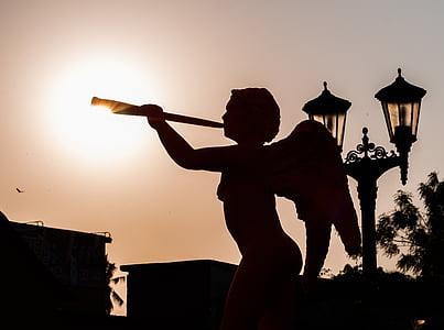 silhouette of cherub holding trumpet figurine