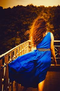 woman wearing blue sleeveless dress