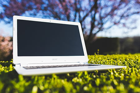 white Acer laptop on grass field