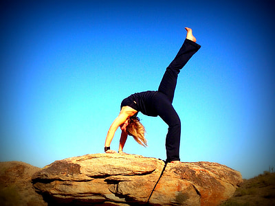 woman doing yoga post on rock formation