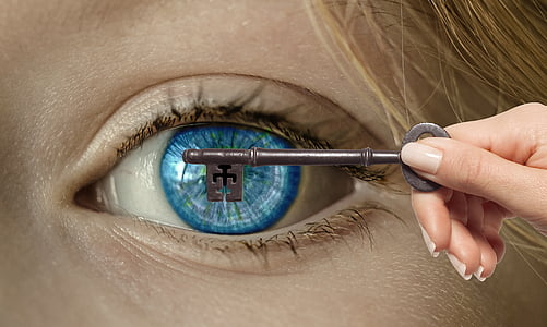 person holding key covering person's left eyeball