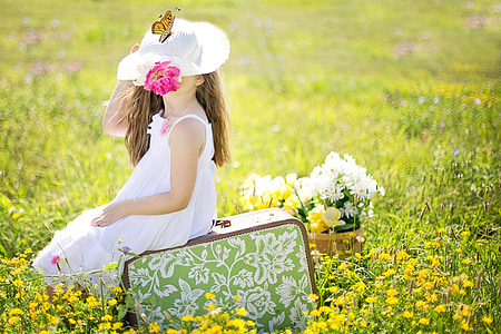 girl wearing white sleeveless dress sitting on green bag