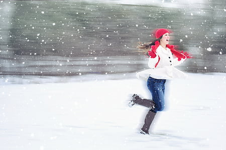 woman in white coat with red scarf with brown boots on snow