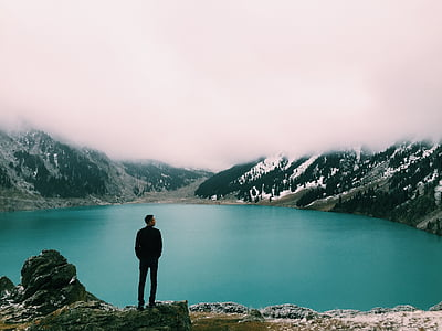 man on top of mountain beaside body of water
