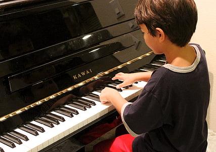 boy wearing black shirt playing Kawai piano