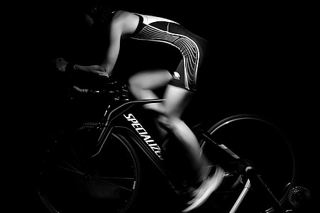 man wearing black and white sleeveless top riding Specialized bike