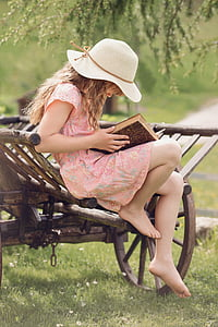 girl in pink and multicolored floral dress holding book sitting on brown wooden carriage