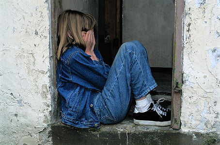 girl in blue jeans and denim jacket with black sneakers covering her face