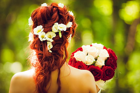 woman holding red and white flower boquet