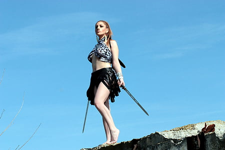 woman in gray halter top holding bladed weapons in both hands