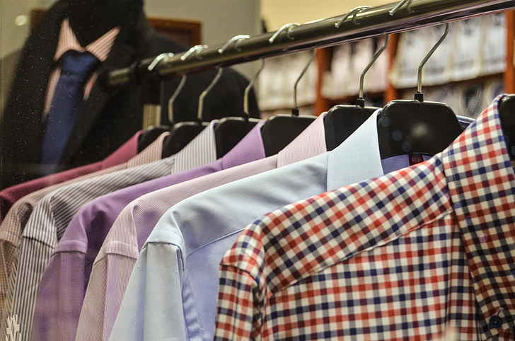 assorted-color dress shirts hanging on clothes rack