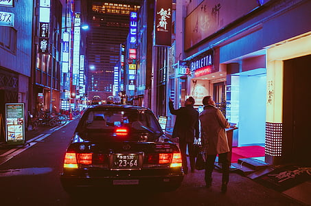 two man beside car staring up on building during nighttime