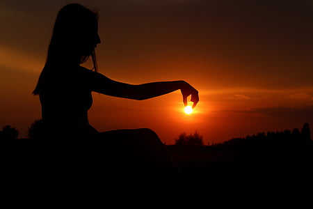 silhouette of woman holding sun