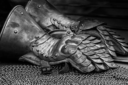 pair of metal gauntlet on chainmail grayscale photography