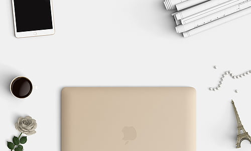 gold Macbook on white textile