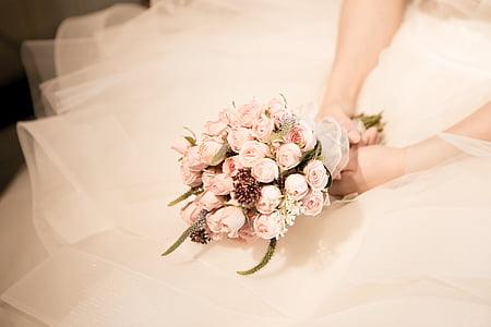 woman wearing wedding dress holding pink rose bouquet