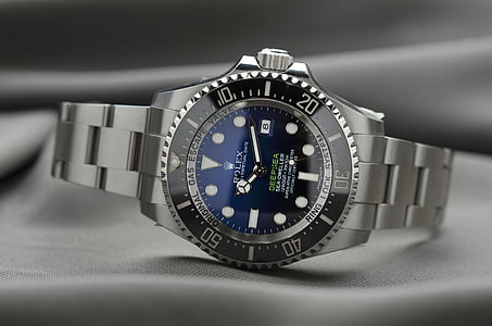 gray Rolex watch reading at 10:12