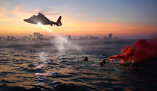 people on ocean with helicopter above them