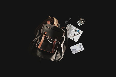 bucket bag beside notebook with pen on top