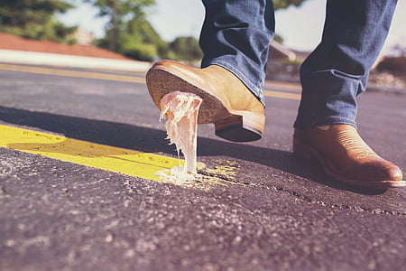 person stepped on white gum near roadside during daytime