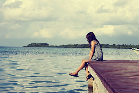 woman in gray dress sitting on dock during cloudy daytime