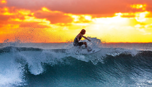 woman surfing during sunset