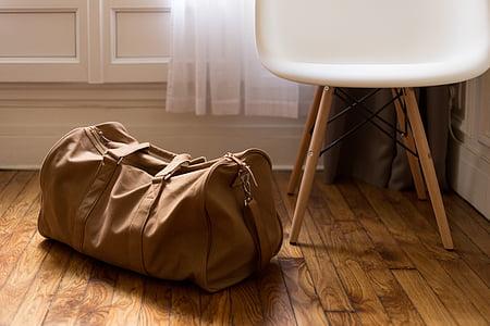 brown duffle bag on floor