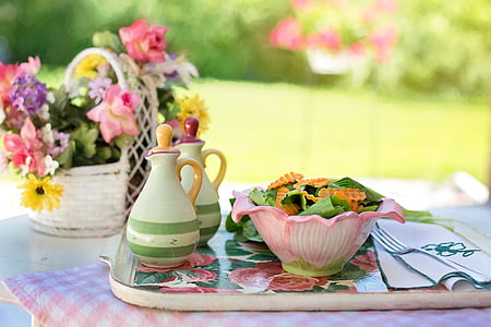pink bowl filled with salad on tray beside table napkin