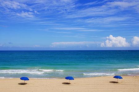 three blue beach umbrellas on seashore under clearsky during daytime