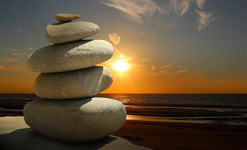 pile of stones on sunset near the seashore