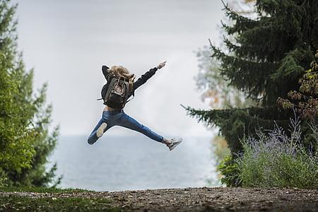 woman wearing blue jeans jumped