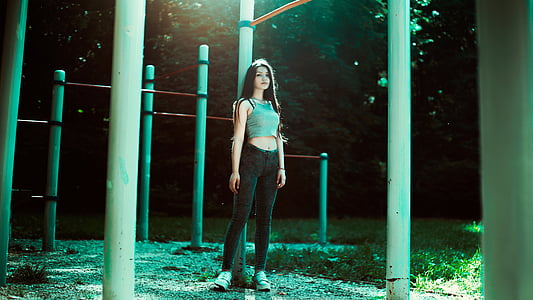 woman wearing teal crop top and black skinny jeans