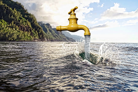 brass faucet and body of water