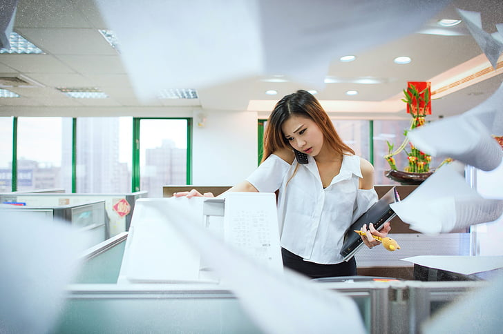 woman wearing white cold-shoulder button-up shirt holding black component and photocopier machine